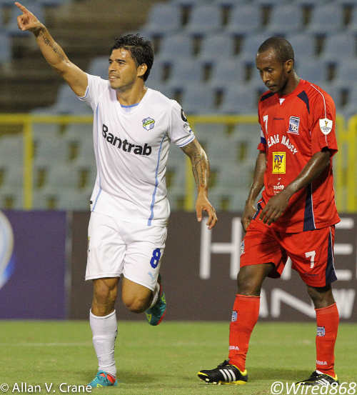Photo: Comunicaciones attacker Paolo Suarez (left) celebrates the second goal in his hattrick while dejected Caledonia AIA skipper Stephan David looks on. (Courtesy Allan V Crane/Wired868)