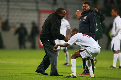 Photo: Former Caledonia AIA head coach Jamaal Shabazz (left) helps defender Kareem Joseph to his feet while assistant coach Rajeesh Latchoo looks on during CONCACAF Champions League action in 2013. (Courtesy Francisco Estrada/Jam MEDIA)