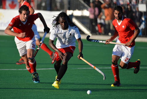 Photo: Trinidad and Tobago star Kwan Browne (centre) glides through the Canada defence. (Courtesy Panamhockey.org)