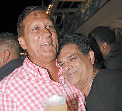Photo: Health Minister Dr Fuad Khan (right) seems to like what he is smelling from business Ish Galbaransingh, who is fighting attempts by the US Government to extradite him for corrupt practices.  Khan certainly knows who to lecture about enjoying State resources. (Courtesy Trinidad Guardian)