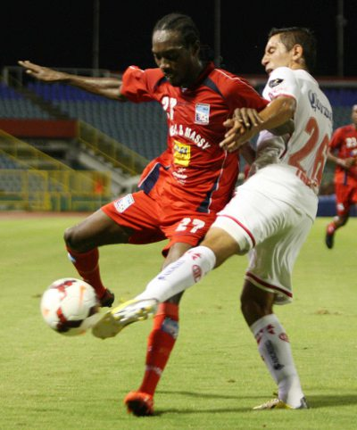 Photo: Caledonia AIA winger Nathan Lewis (left)  tries to get past Toluca midfielder Erbin Trejo. (Courtesy Wired868)