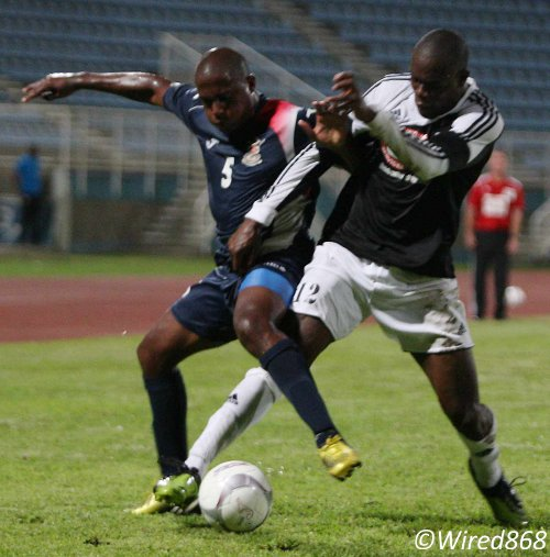 Photo: Central FC defender Jamal Jack (right) tussles with Defence Force player Devin Jordan during their opening fixture. (Courtesy Wired868)