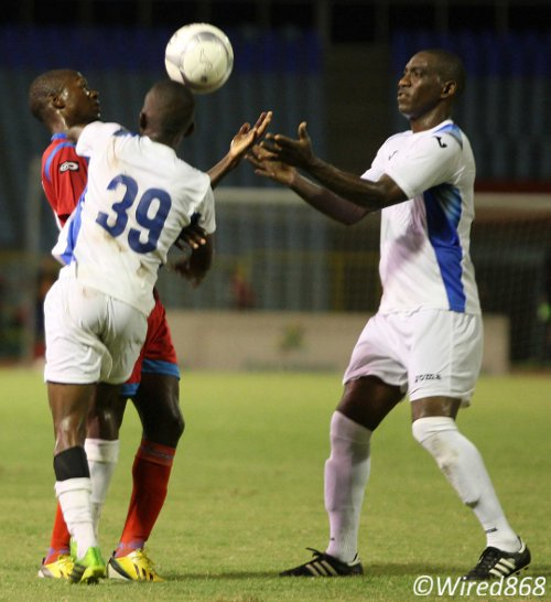 Photo: Police midfielders Trent Noel (right) and Joel Lewis (number 39) try to wrestle the ball from St Ann's Rangers attacker Kennedy Isles. (Courtesy Wired868)