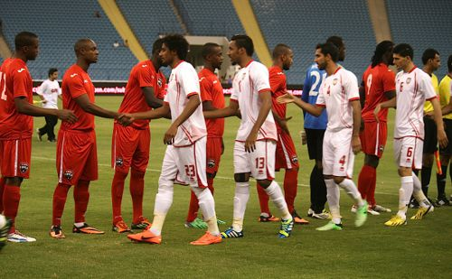 Photo: The Trinidad and Tobago and United Arab Emirates teams exchange pleasantries before kick off. (Courtesy TTFA Media)