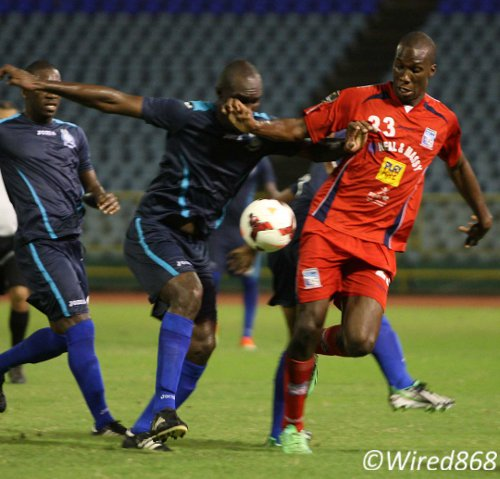 Photo: Caledonia AIA strikre Jamal Gary (far right) battles for possession against Police FC defenders. (Courtesy Wired868)