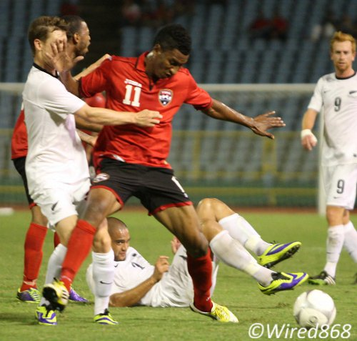 Photo: Trinidad and Tobago attacker Willis Plaza (second from left) holds off a New Zealand opponent during an international friendly at the Hasely Crawford Stadium. (Courtesy Wired868)