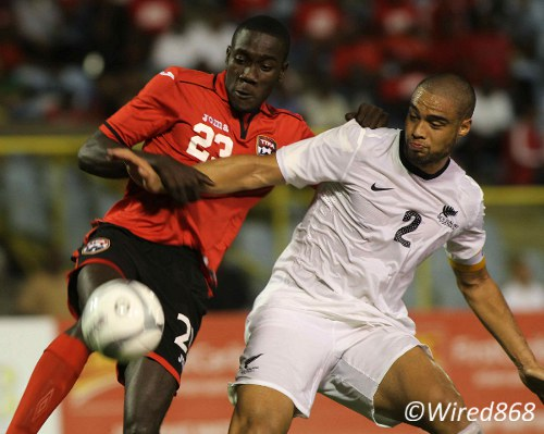 Photo: Nineteen year old Trinidad and Tobago striker Rundell Winchester (left) tussles with New Zealand captain and West Ham defender Winston Reid during his senior international debut. (Courtesy Wired868)