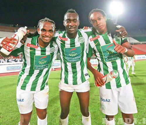 Photo: Trinidad and Tobago defender Akeem Adams (far left) celebrates with two teammates during his brief playing stint with Hungarian club, Ferencvarosi. At present, Adams is waiting for a heart transplant after having his left leg amputated last month. (Courtesy Fradi.hu)