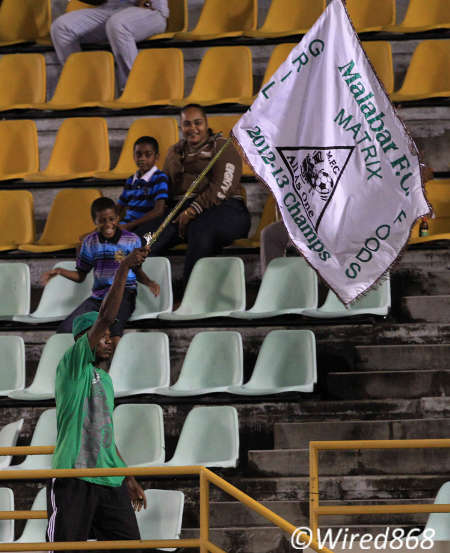 Photo: A Malabar FC supporter waves the flag for the Super League team. (Courtesy Allan V Crane/ Wired868)