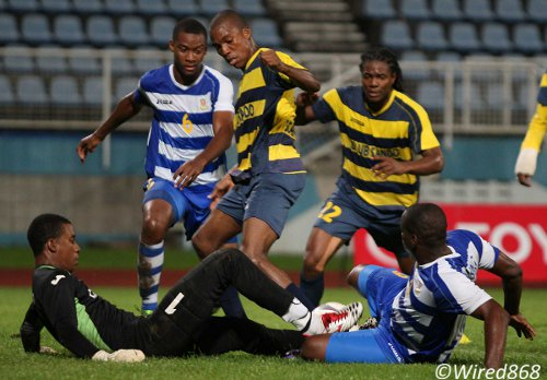 Photo: Club Sando goalkeeper Andre Marchan (bottom left) uses his feet to block Defence Force striker Devorn Jorsling (bottom right) while Rodell Elcock (left), Kern Cupid (centre) and Coneal Thomas look on. (Courtesy Wired868)