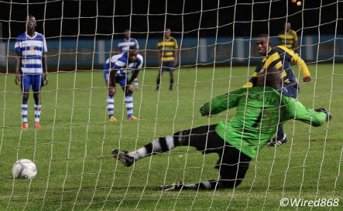 Photo: Club Sando midfielder Anthony Parris (right) places his penalty past Defence Force goalkeeper Kevin Graham. (Courtesy Wired868)
