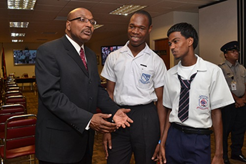 Photo: Former House Speaker Wade Mark (left) talks to students in Parliament. Education is not presumed to be an important factor for voters. (Courtesy Gov.tt)