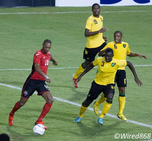 Photo: Trinidad and Tobago playmaker Ataullah Guerra (left) drives past a crowd of Jamaican defenders for the opening goal last night. (Courtesy Allan V Crane/Wired868)