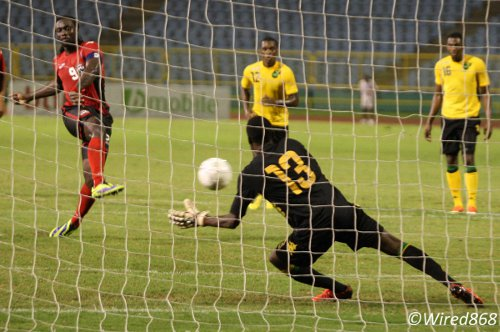 Photo: Trinidad and Tobago captain Kenwyne Jones (background) strokes a penalty past Jamaica goalkeeper Richard McCallum in a 2-0 friendly win on November 19. (Courtesy Wired868)