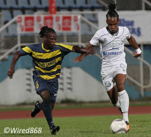 Photo: W Connection forward Neil Benjamin (right) tries to drive past Club Sando left back Kemuel Rivers. (Courtesy Wired868)