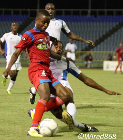 Photo: St Ann's Rangers utility player Clevon McFee (left) tries to evade a tackle from the Police defender during a previous Pro League fixture. (Courtesy Wired868)