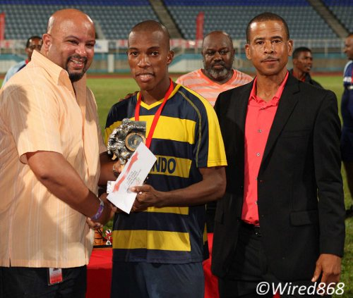 Photo: Club Sando right back Kern Cupid (centre) was adjudged the Toyota Classic's MVP. Pro League CEO Dexter Skeene (right) looks on. (Courtesy Wired868)