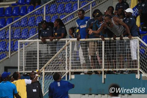 Photo: A Club Sando supporter is restrained as he gesticulates towards Caledonia AIA coach Jamaal Shabazz (bottom right) and player Abdallah Phillips (bottom second from left). (Courtesy Allan V Crane/Wired868)