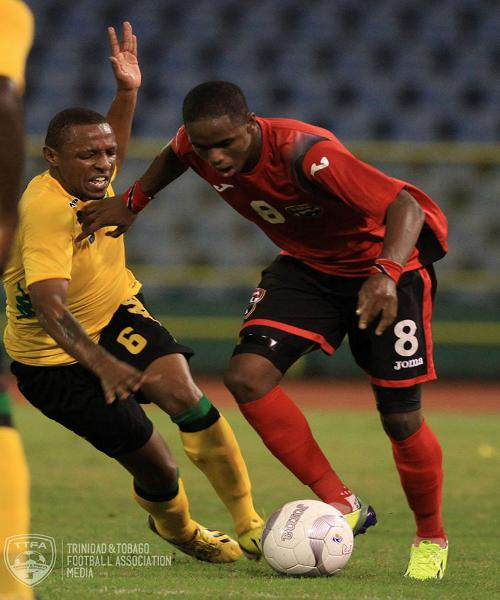 Photo: Trinidad and Tobago utility player Joevin Jones (right) drives past Jamaica midfielder Jermaine Woozencroft during a friendly international in Port of Spain on 19 November 2013. (Courtesy Allan V Crane/TTFA Media)