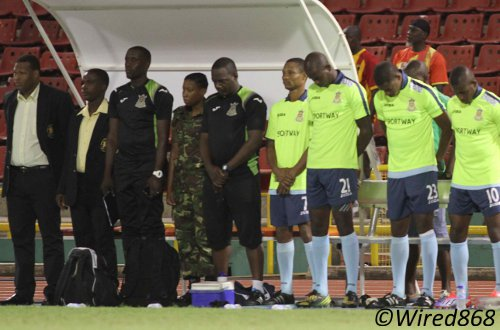 "Photo: Defence Force coach Marvin Gordon (far left) leads his bench in observing a minute's silence for former soldier Rawle Fletcher and ""Soca Warrior"" defender Akeem Adams. (Courtesy Wired868)"