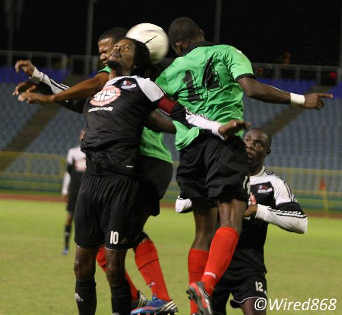 Photo: Veteran Central FC playmaker Marvin Oliver (foreground) attempts a back header under pressure from San Juan Jabloteh's Shaquille Bertrand (no 14) and his teammate. (Courtesy Wired868)