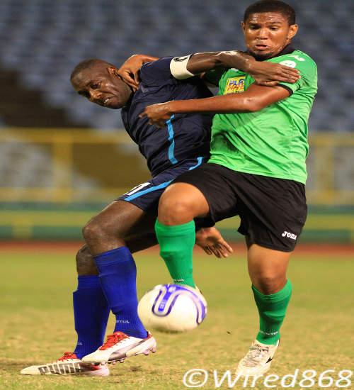 Photo: Police FC captain Todd Ryan (left) battles for possession with San Juan Jabloteh mdifielder Jean-Luc Rochford. (Courtesy Allan V Crane/Wired868)