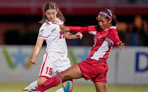 Photo: Trinidad and Tobago captain Anique Walker (left) fights for the ball with Cayman Islands defender Amanda Nelson. (Courtesy CONCACAF.com)