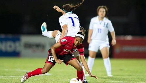 Photo: Trinidad and Tobago midfielder Shanisa Camejo (foreground) tangles with Honduras striker Lauren Hall during their group opener. (Courtesy MexSport/CONCACAF)