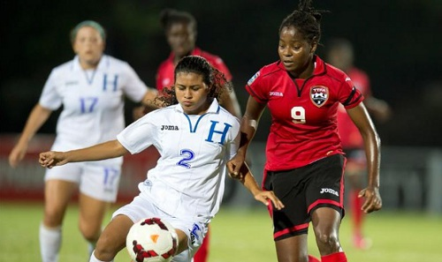 Photo: Trinidad and Tobago's winged terror Patrice Campbell (right) puts pressure on Honduran player Dania Reyes during their group opener, which T&T won 2-0. (Courtesy CONCACAF.com)