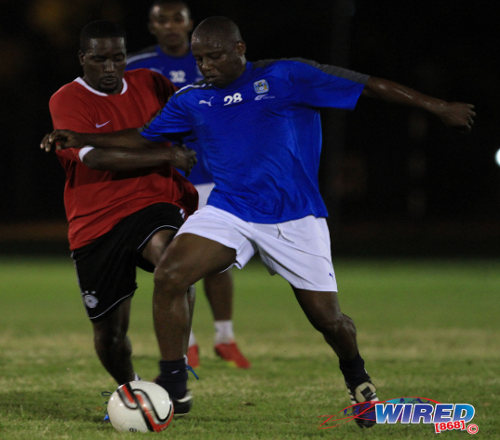 "Photo: Trinidad and Tobago assistant coach and former Strike Squad star Hutson ""Barber"" Charles (right) holds off ex-SSFL standout and festival MVP Lorne Joseph. (Courtesy Allan V Crane/ Wired868)"