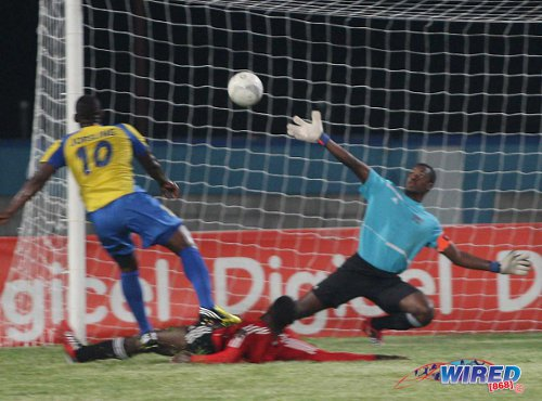 Photo: Defence Force striker and one of the Pro League's most prolific marksmen Devorn Jorsling (left) hammers the ball past ex-Central FC goalkeeper Marvin Phillip. (Courtesy Wired868)
