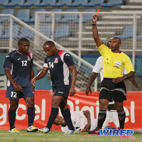 Photo: Referee Neal Brizan (right) flashes red at Defence Force captain Cory Rivers (centre) during a Pro League match last season. Brizan is widely regarded as one of the country's finest officials but he was fiercely criticised last night. (Courtesy Wired868)