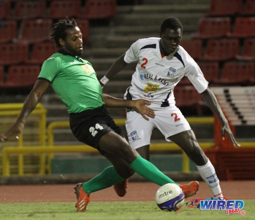 Photo: San Juan  Jabloteh defender Kareem Smith (left) tries to keep the ball from Caledonia AIA defender Aubrey David. (Courtesy Wired868)