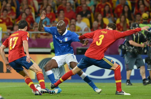 Photo: Italy star Mario Balotelli (centre) tries to dance between Spain defenders Gerard Piqué (right) and Álvaro Arbeloa. (Courtesy Gabriel Bouys/ AFP)