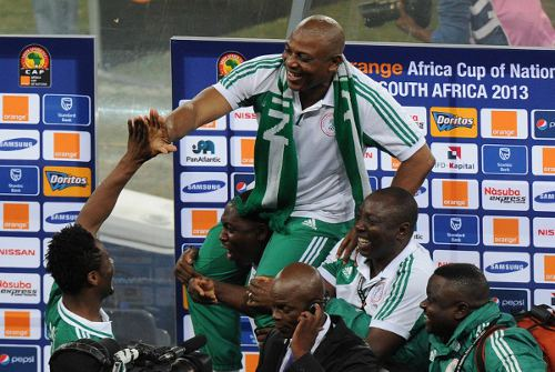 Photo: Nigeria coach Stephen Keshi is held aloft by staff members while star midfielder John Obi Mikel (far left) offers his congratulations. (Courtesy Alexander Joe/ AFP)