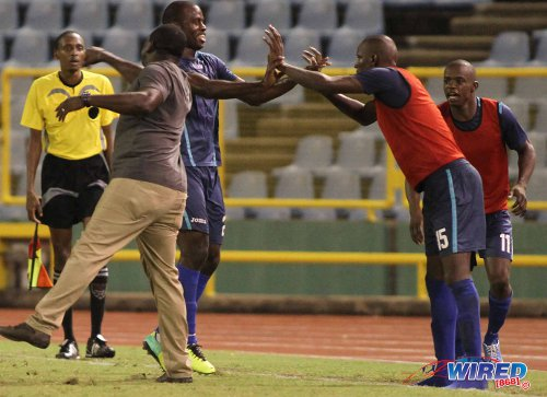 Photo: Police coach Richard Hood (left) tries to join the celebrations while Elijah Belgrave (centre) is congratulated by substitute Jameel Perry during a previous Pro League fixture. (Courtesy Wired868)