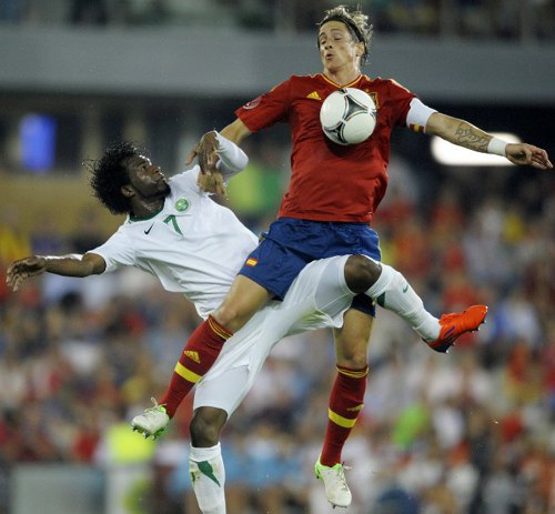 Photo: Ouch! Spain's Fernando Torres (right) takes a blow to the jewels from Saudi Arabia's Kamil Al-Mousa during an international friendly.  Torres looks set to miss the 2014 World Cup due to the controversial recruitment of Brazil-born striker Diego Costa. (Copyright AFP 2014: Miguel Riopa)