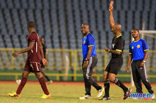 Photo: Referee Neal Brizan (second from right) flashed red at North East Stars midfielder Keithy Simpson (far left) while head coach Angus Eve (second from left) and assistant coach Kendall Velox watch on. (Courtesy Allan V Crane/ Wired868)