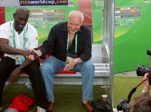 "Photo: Ex-Togo coach Otto Pfister (right) shakes hands with assistant Kodjovi Mawuena at the 2006 World Cup. Pfister, a German by birth, coached nine African nations. But he led the ""Soca Warriors"" to a first round 2014 World Cup elimination at the hands of Trinidadian Jamaal Shabazz's Guyana team. (Courtesy Philippe Huguen/ AFP)"