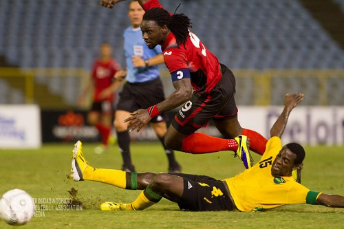 Photo: Trinidad and Tobago captain Kenwyne Jones tries to hurdle Jamaica captain Je-Vaughn Watson during a friendly international at the Hasely Crawford Stadium last November. Jones was selected as the TTFA's 2013 Player of the Year. (Courtesy Allan V Crane/TTFA Media)