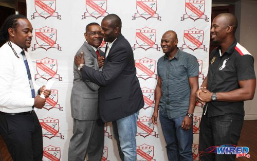 Photo: TTFA president Raymond Tim Kee (second from left) embraces 2006 World Cup player Kelvin Jack while teammates Brent Sancho (far left), Cyd Gray (second from right) and David Atiba Charles look on in May 2013. The TTFA has not fulfilled its obligations to the World Cup players since its initial payment to the players. (Courtesy Wired868)