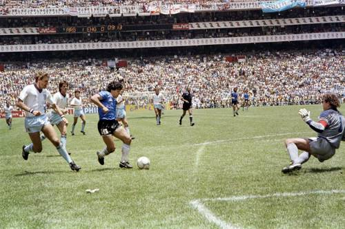 Photo: Argentina legend Diego Maradona (centre) is about to drag the ball past England goalkeeper Peter Shilton (right) while defenders Terry Butcher (far left) and Terry Fenwick (second from left) look on. (Copyright AFP 2014)