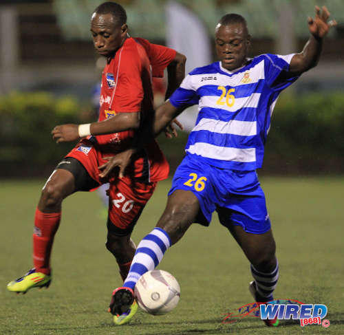 Photo: Defence Force forward Richard Roy (right) holds off Caledonia AIA utility player Noel Williams in a previous clash. Roy scored twice against St Ann's Rangers tonight. (Courtesy Allan V Crane/Wired868)