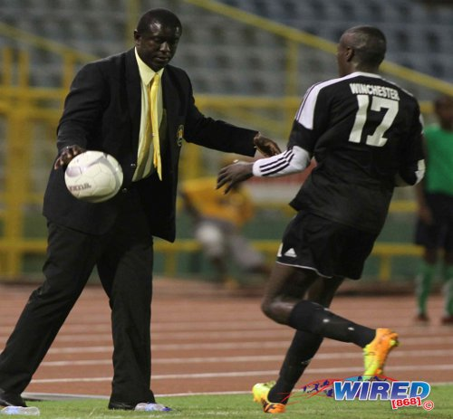 Photo: Then Defence Force coach Ross Russell (left) stops the ball for Central FC forward Rundell Winchester during the 2013/14 Pro League season. (Courtesy Wired868)