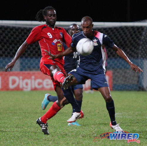 Photo: Defence Force winger Jemel Sebro (right) screens the ball away from Caledonia AIA attacker Keyon Edwards during a league match last season. (Courtesy Wired868)