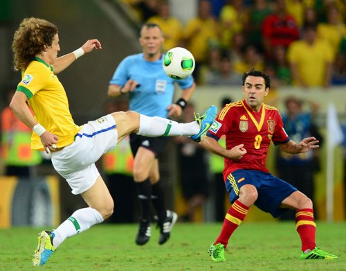 Photo: Brazil defender David Luiz (left) beats Spain midfielder Xavi to the ball during the 2013 FIFA Confederations Cup final. (Copyright AFP 2014/ Christophe Simon)