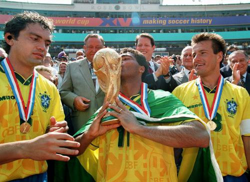 Photo: Brazil legend Romario (centre) kisses the 1994 World Cup trophy while Branco (left) and captain Dunga look on. (Copyright AFP 2014/Timothy A Clary)