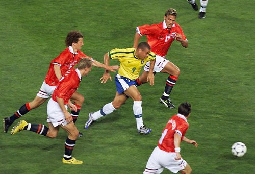 Photo: Brazil forward Ronaldo (centre) charges past the Norwegian quartet of Havard Flo (right rear), Dan Eggen (far left), Kjetil Rekdal (second from left) and Oyvind Leonhardsen during the 1998 World Cup. (Copyright AFP 2014: Georges Gobet)