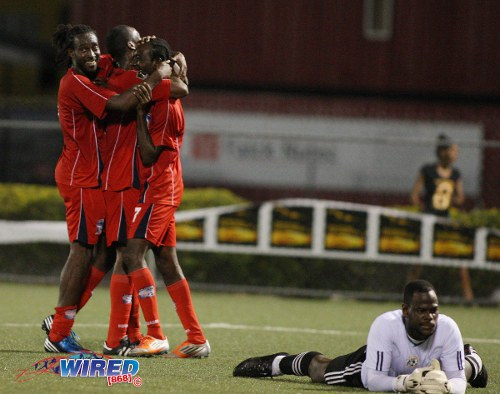 Photo: Caledonia AIA players celebrate at the expense of Jan-Michael Williams (right) during the latter's stint at St Ann's Rangers last year. (Courtesy Wired868)