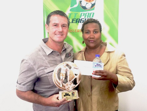 Photo: Central FC coach Terry Fenwick (left) receives his Blue Waters Coach of the Month award from Pro League secretary Julia Baptiste. (Courtesy TT Pro League)